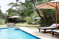 Sun loungers are placed beside a swimming pool in the grounds of a luxury guest house. Red cedar tables laid for dinner and shaded by parasols are dotted around the garden.