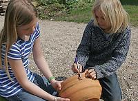 """Kinder bauen eine Sonnenuhr, auf einem Blumentopf wird ein """"S"""" für Süden gemalt"""