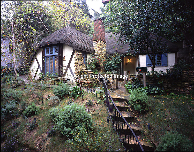 This cozy abode, reminiscent of an English Cotswold cottage is tucked into a ravine just below the Hollywood sign in Los Angeles. The Hollywood sign originally read ìHollywoodlandî and was an advertisement for a housing development begun in 1923. Originally the development was supposed to contain mostly romantic and Storybook style homes, but as budgets and pocketbooks tightened during the Great Depression, regulations were relaxed and more pedestrian homes were built. Still there are many wonderful homes to see in the area and the Storybook style sleuth will be rewarded with glimpses of fanciful homes once owned by stars like Humphrey Bogart, Gloria Swanson and Bela Lugosi. Even Madonna owned one of the larger homes for a while.
