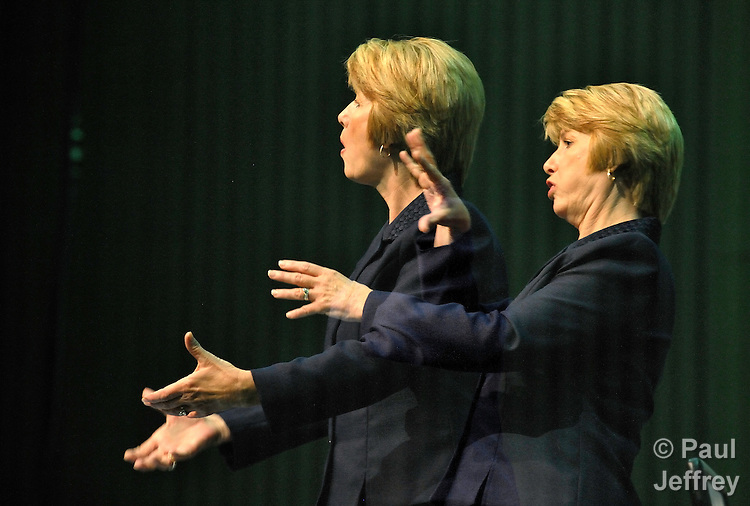 A double exposure of Barbara Steinbrenner, a member of Oak Park United Methodist Church in Temple, Texas, as she translates into American Sign Language during the 2008 United Methodist General Conference in Fort Worth, Texas, on May 1.