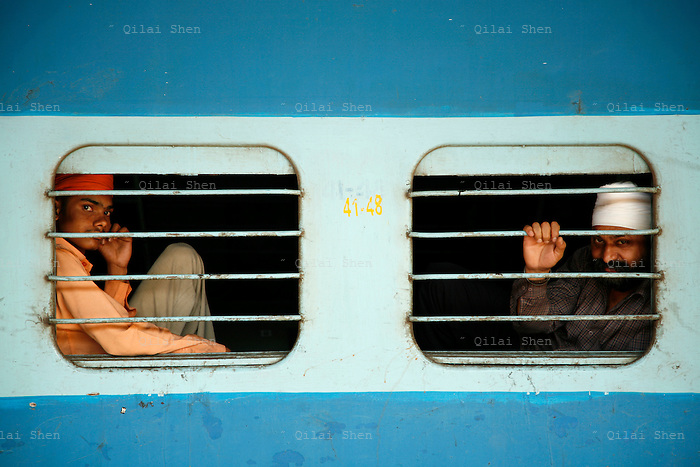 Passengers sit near windows while waiting for their train to depart at the Chhartrapati Shivaji Terminus, also known as the Victoria Terminus, in Mumbai, India on Sunday, 31 December 2006.