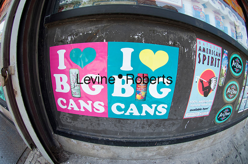 """Advertisements for Arizona beverages seen outside a grocery store in the Lower East Side in New York on Saturday, May 26, 2012.  Some people complain the advertising campaign """"I Love Big Cans"""" is demeaning to women.  (© Frances M. Roberts)"""