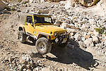 A yellow Jeep with the Motherlode Rock Crawlers travels a rough rock-piled road in the Argus Range to climb to site of Historic Lookout City and the Modoc Mine.