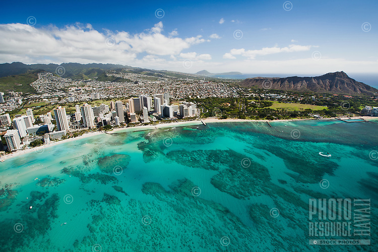 Aerial view of the Diamond Head side of Waikiki Strip and Beach, O'ahu; surfers and swimmers can be seen among the reef-strewn waters.