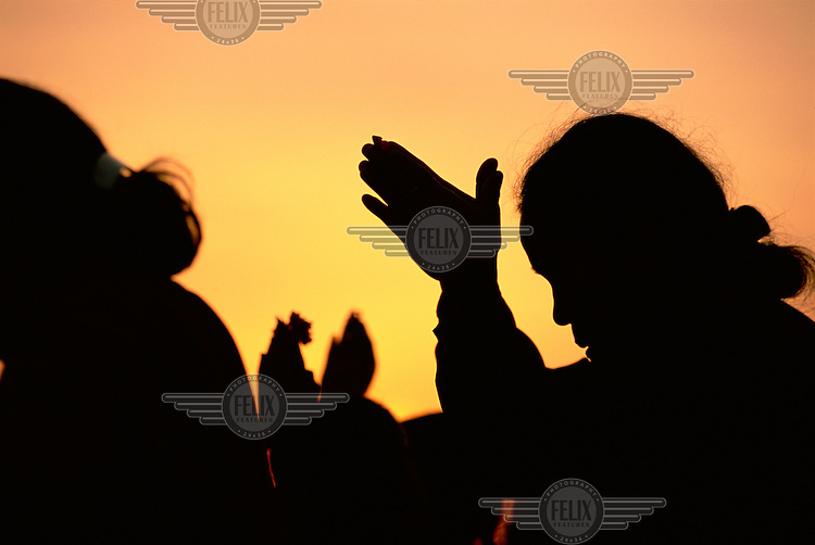 A Balinese Hindu worshipper is silhouetted against the sun while making an offering at a temple at sunset.