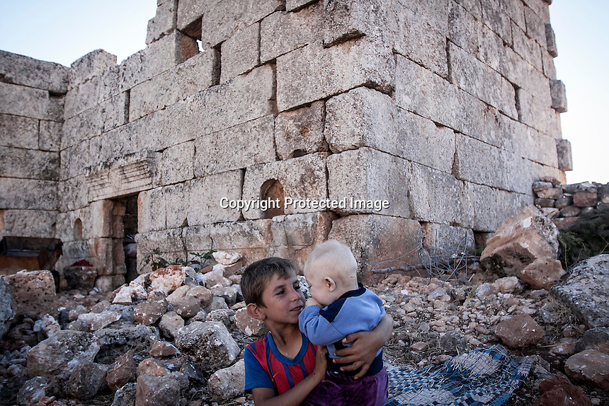 """In this Friday, Sep. 27, 2013 photo, a Syrian displaced child plays with his baby brother at the Kafr Ruma, an ancient roman ruins used as temporary shelter by those families who have fled from the heavy fighting and shelling in the Idlib province countryside of Syria. Dozens of families settled in the ancient ruins known as """"The Forgotten City"""" and declared human heritage by UNESCO, when the clashes between opposition fighters and government forces broke out in the region since more than two years ago. (AP Photo)"""