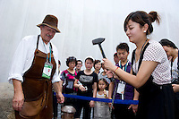Blacksmith Matti Olkkonen (left) helps Finland's Pavilion's 4 millionth visitor Liu Xin (right) to coin a souvenir coin, in Finnish Pavilion 'Kirnu' on Shanghai World Expo 2010 site, in Shanghai, China, on September 19, 2010. Photo by Lucas Schifres/Pictobank