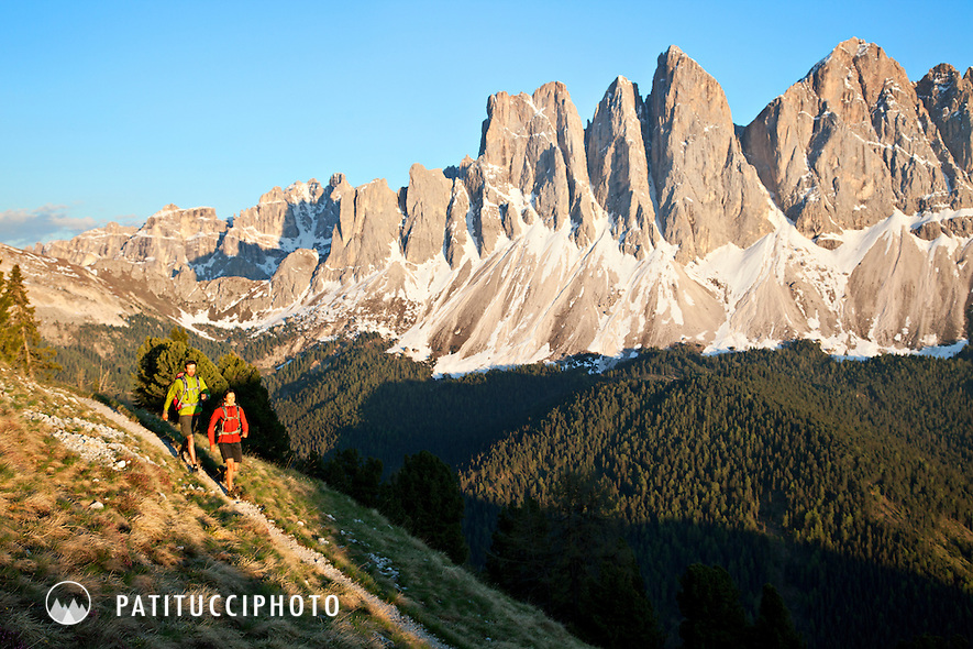 Couple hiking on the Gunther Messner Höhenweg high above the Villnosstal/Val di Funes in the Italian Dolomites with the Geisler/Odla Group behind at sunset