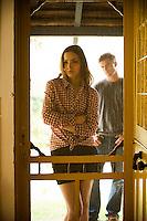 Young woman standing in front of screen door, man seen in background