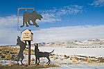 Two silhouette dogs tree a cougar above the mailbox of the Holland Ranch along the highway in northern Nevada.