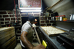 A Palestinian man bakes traditional bread during the holy month of Ramadan in Jerusalem's old city, 12 July 2013. Muslims around the world are observing the holy fasting month of Ramadan in which they refrain from eating, drinking, sex and smoking from dawn to dusk. Photo by Saeed Qaq
