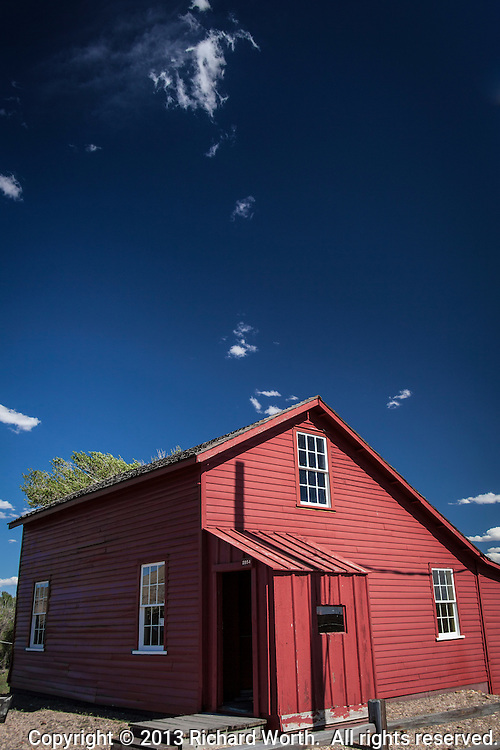 """The Bridge Tender""""s House at Fort Fred Steele, near Rawlins, Wyoming.  Red clapboard house with blue sky and a few puffy clouds."""
