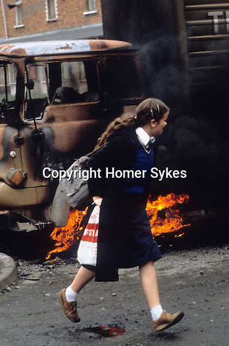 Belfast The Troubles 1980s. School girls rushes past a burning hijacked lorry used as a barricade across the road. Northern Ireland.