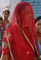 woman in red sari visiting camel fair in holy city Pushkar, Rajastan, India