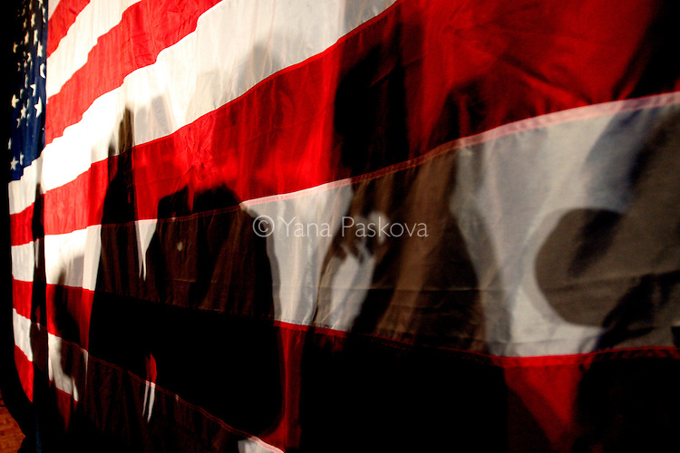 Supporters' shadows of Republican presidential hopeful and former Massachusetts Governor Mitt Romney meet the flag during a campaign stop at Simpson College in Indianola, Iowa June 30, 2007.