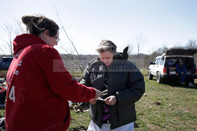 Residents of East Bernstadt in Laurel County, Ky. pick up debris on March 3 following the March 2, 2012 tornado in which five people in the county died. Photo by Latara Appleby | Staff ..