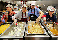NWA Democrat-Gazette/DAVID GOTTSCHALK  Tina Thompson (from left), Carol Phillips, Michele Lee and Peggy Walker prepare meals Tuesday, November 24, 2015, during the Samaritan Community Center  annual Thanksgiving Dinner in Springdale. Seven hundred meals were served in the Springdale location with all of the food provided by the Walmart Transportation Operations, Special Projects and Fixtures Division. Five hundred Blessing Bags, donated items from Walmart ISD containing all of the ingredients for a traditional Thanksgiving Meal, were also distributed during the meal.