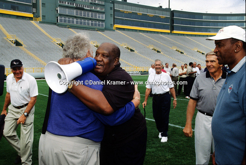 Former Packers Paul Hornung and Willie Davis embrace in Lambeau Field for part of the Lombardi Legends reunion in September of 2001.