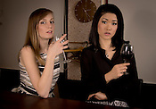A caucasian and Japanese woman in a bar with wine.