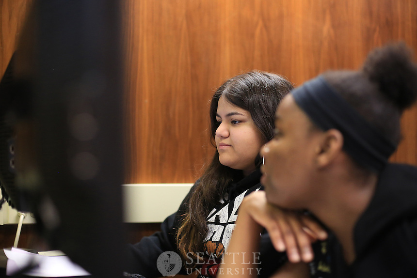 12042012-  Middle College High School at Seattle University..Middle College High School senior Kymberli Gonzalez, center, works on her paper as fellow student, Nahje Taylor-Woods watches during class Dec 4, 2012.