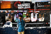 A street child is seen in front of a poster of a Bollywood film, Mumbai Meri Jaan (Mumbai My Love!).