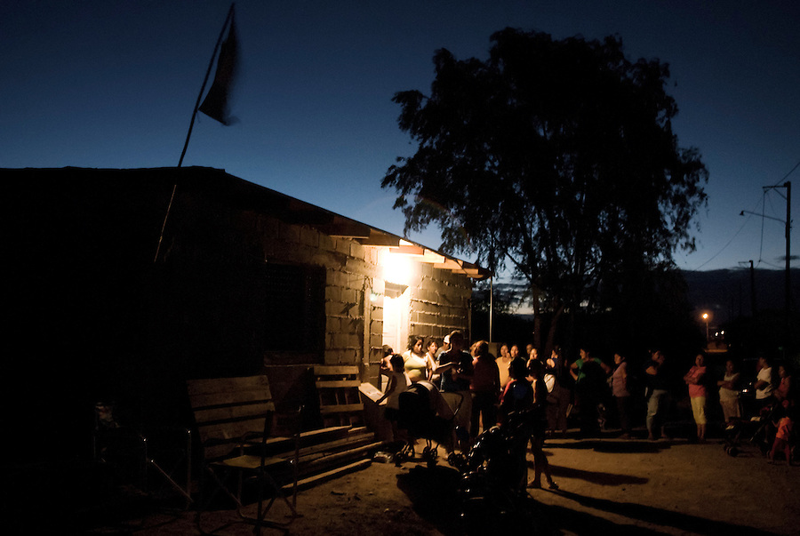 """Villa El Libertador, Cordoba, Argentina...""""If the life we live is not dignified, our dignity is the struggle to change it."""".The line of people waiting to discuss their future house in """"El Libertador"""" with the cooperative that organized the take..La Toma - the take of a piece of land, left uncultivated for years by the great soya entrepreneurs in Argentina. Around 250 families have decided to take the situation in their own hands, fighting to gain the right to have a house, while waiting for the state and the local authorities to face the serious living conditions and disoccupation problems in the shantytowns of Argentinas second biggest city Cordoba."""