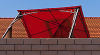 A sudden gust of wind blew over this red movable patio cover (big umbrella, or whatever you want to call it), so it's now sitting askew on its side.