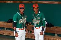 Greensboro Grasshoppers Marcos Rivera (11) and Jose Devers (2) pose for a photo in the dugout before a game against the Lakewood BlueClaws on June 10, 2018 at First National Bank Field in Greensboro, North Carolina.  Lakewood defeated Greensboro 2-0.  (Mike Janes/Four Seam Images)