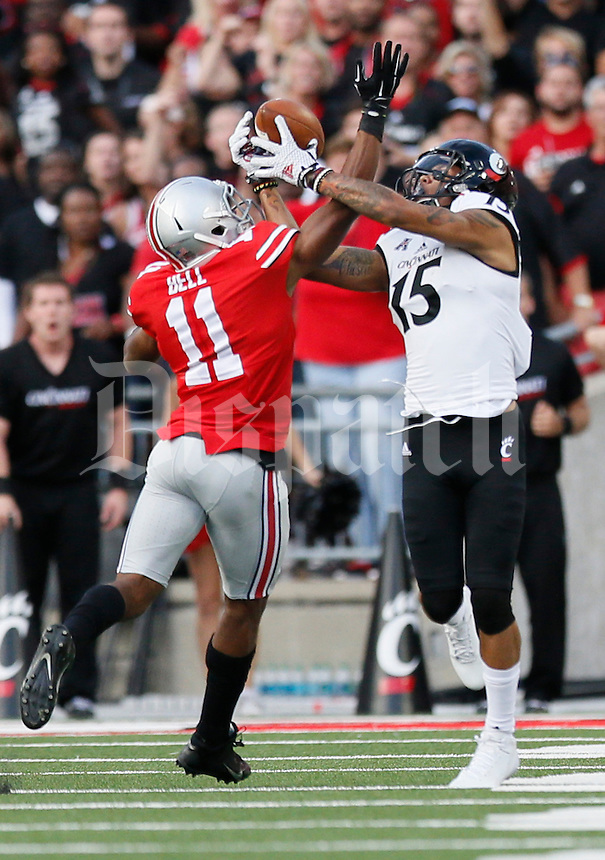 Cincinnati Bearcats wide receiver Chris Moore (15) catches the first touchdown pass over Ohio State Buckeyes defensive back Vonn Bell (11) during the 1st quarter of a football game between The Ohio State Buckeyes and the University of Cincinnati Bearcats on Saturday, September 27, 2014 at Ohio Stadium in Columbus. (Columbus Dispatch photo by Fred Squillante)