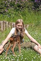 Rehkitz, Reh-Kitz, verwaistes, pflegebedürftiges Jungtier wird in menschlicher Obhut großgezogen, Kind, Mädchen spielt mit Kitz im Garten, Kitz, Tierkind, Tierbaby, Tierbabies, Europäisches Reh, Ricke, Weibchen, Capreolus capreolus, Roe Deer, Chevreuil
