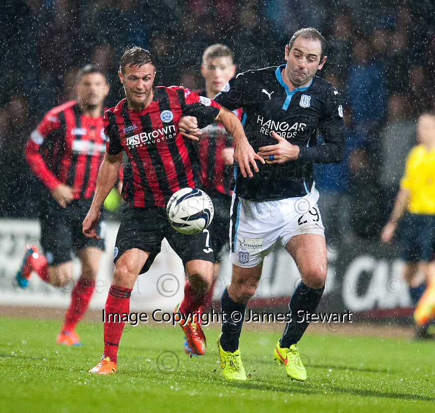 St Johnstone's Chris Millar and Dundee's Gary Harkins challenge for the ball.