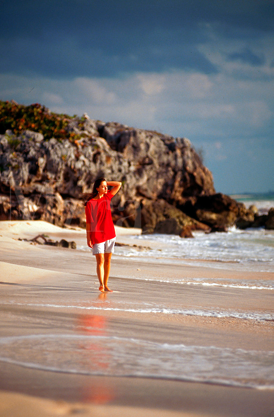 Woman walking in surf along beach. Mexico.