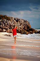 Woman walking in surf along beach. Mexico.