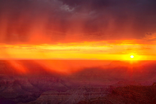 Sheets of rain appear red during sunset at Point Sublime at the North Rim of Grand Canyon National Park, Arizona