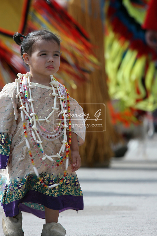 A young female Native American child in front of dancers at a Pow Wow at the Milwaukee Lakefront Indian Summer Festival, Wisconsin