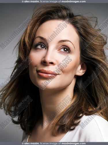 Portrait of a beautiful smiling woman with daydreaming expression