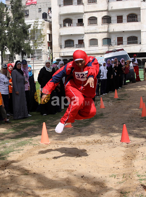 A Palestinian woman competes barefoot in the long jump during a local athletics competition at Palestine Stadium in Gaza City on May 8, 2010. Photo by Mohammed Asad
