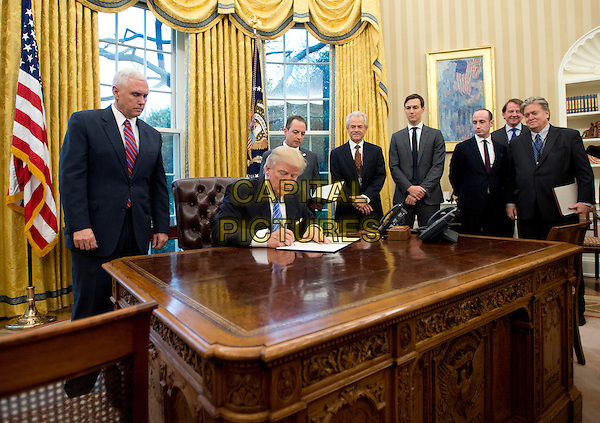 United States President Donald Trump signs the first of three Executive Orders in the Oval Office of the White House in Washington, DC on Monday, January 23, 2017.  They concerned the withdrawal of the United States from the Trans-Pacific Partnership (TPP), a US Government hiring freeze for all departments but the military, and &quot;Mexico City&quot; which bans federal funding of abortions overseas.  Standing behind the President, from left to right: US Vice President Mike Pence; White House Chief of Staff Reince Preibus; Peter Navarro, Director of the National Trade Council; Jared Kushner, Senior Advisor to the President; Steven Miller, Senior Advisor to the President; unknown; and Steve Bannon, White House Chief Strategist.<br /> CAP/MPI/CNP/RS<br /> &copy;RS/CNP/MPI/Capital Pictures