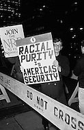 09 Dec 1969, Manhattan, New York City, New York State, USA. An American protester holds a sign with Racial Purity is America's Security written on it while marching in front of the Waldorf Astoria Hotel where President Nixon is attending a National Football Foundation Dinner. President Nixon had promised an early end to the Vietnam war but in a speech on November 3 in 1969 he announced his plan of Vietnamization and continuation of the war and many protesters took to the streets later in the month to express their dissatisfaction.