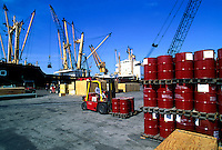 A forklift operator moves 55 gallon drums on shipping pallets. A ship and cranes are visible behind the loading dock.
