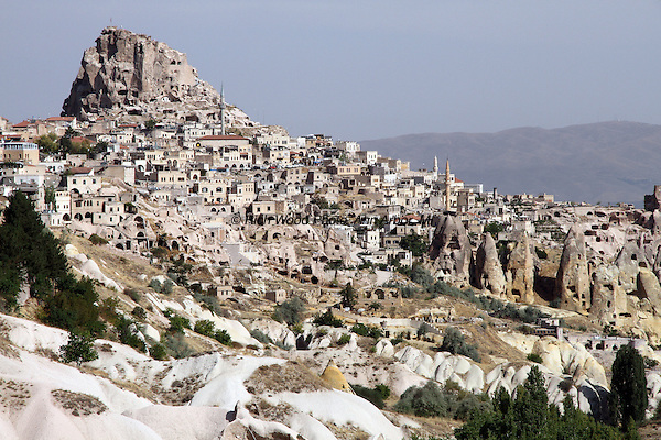 Homes cut into rock on a hillside of Turkey in the Cappadocia region