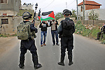 Palestinian protesters wave their national flag in front of Israeli security forces during a protest marking the Palestinian Land Day in the West Bank village of Nabi Saleh near Ramallah, March 28, 2015. Land Day commemorates the unrest that erupted in March 1976 when Israeli Arabs protested the Israeli government's confiscation of thousands of acres of Arab-owned land and in which six Arab citizens were killed by Israeli police. Photo by Shadi Hatem
