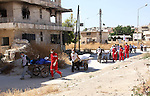 Red Crescent workers carry the bodies of dead fighters loyal to Free Syrian Army on carts during an exchange of dead bodies between Free Syrian Army and Syrian Government forces, in Bustan al-Qasr district in the east of the northern Syrian city of Aleppo on June 11, 2015. Photo by Ameer al-Halbi