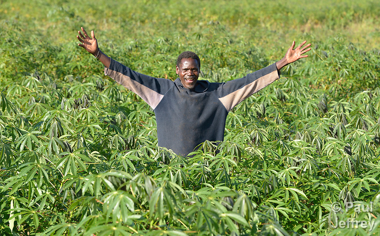 Chomex Nkhambule poses on his farm in Edundu, Malawi. He and others in the village have benefited from intercropping, crop rotation, and composting practices they learned from the Malawi Farmer-to-Farmer Agro-Ecology project of the Ekwendeni Mission Hospital AIDS Program, a program of the Livingstonia Synod of the Church of Central Africa Presbyterian. The new farming skills and techniques convinced Nkhambule to come back to the village from South Africa, where he was working and sending remittances home.
