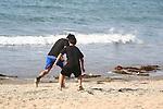 TWO CHILDREN PLAY SOCCER ON OCEANS EDGE