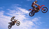 A pair of motocros racers fly torugh the blue Florida sky during a supercross race in Daytona Beach, FL.  (Photo by Brian Cleary/www.bcpix.com)