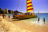 Tourists gather on the deck of a large catamaran with a red and yellow striped sail on the beach at Waikiki. People walking on the beach, Waikiki hotels and Diamond Head complete the background.