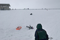 Sledders on the downside of Hoover Reserpoir Dam after a snow storm.