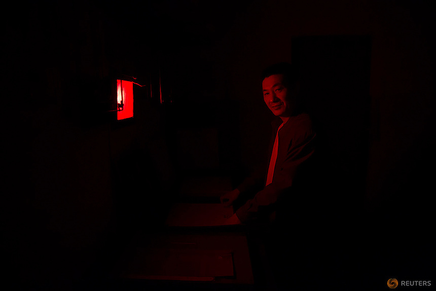 Yang Yang, a x-ray technician poses for picture under the red light of his lab at radiology department of Yangjia Hospital in Wuji County, China's Zhejiang Province October 19, 2015. Behinds walls and broken windows of radiology department covered with creeping vines, a single member of staff and a single X-ray machine serve few remaining pneumoconiosis patients of Yangjia Hospital. The hospital, once considered top medical institution with latest imported equipment became private after the mine company that built it went broke in 2001. Since that time Yangjia Hospital is not able to keep the high standards and is now offering only basic care for its remaining patients.    REUTERS/Damir Sagolj