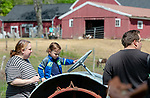 WOODBURY,  CT-051819JS02- Alaric Morehouse, 3, of Watertown site on an hold tractor as his mom, Robin Masiewicz Morehouse, left, looks on, during the annual Flanders Festival:  A Celebration of Art, Farming &amp; Nature at the Flanders Nature Center in Woodbury on Saturday. <br /> Jim Shannon Republican American